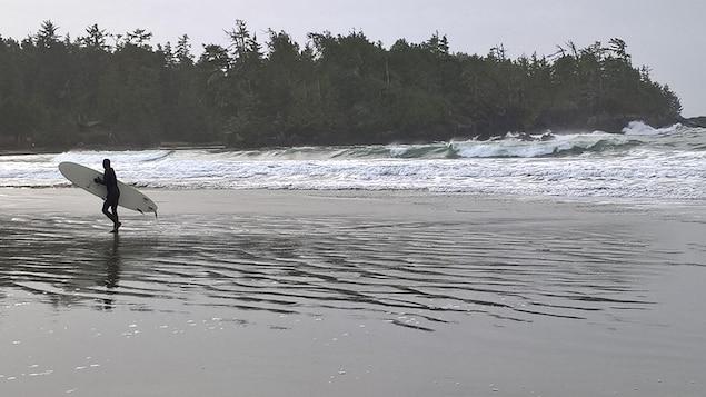 Un surfeur marche sur la plage avec sa planche sous le bras après être sorti de l'eau à Tofino, en Colombie-Britannique.