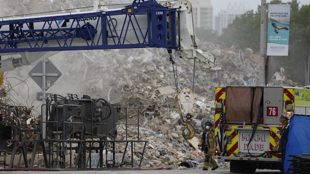 Un pompier marche près des décombres de l'immeuble.