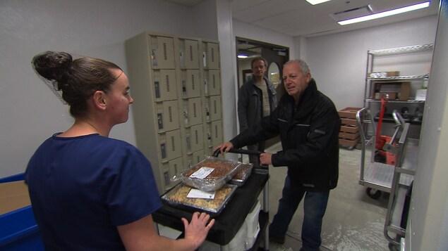 Une jeune employée de l'hôpital amène sur un chariot des surplus de nourriture à un représentant d'organisme communautaire.