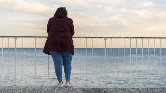 Une femme regarde la mer qui s'étend devant elle.