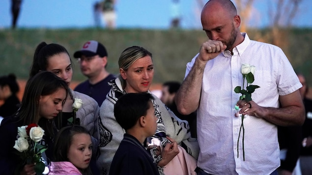 Un homme porte une rose blanche, il pleure, accompagné de ses enfants et de sa femme.