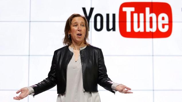 Susan Wojcicki est debout devant un écran sur lequel est affiché le logo de YouTube.