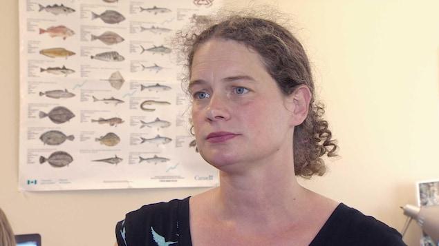 Susanna Fuller devant une affiche sur les poissons.