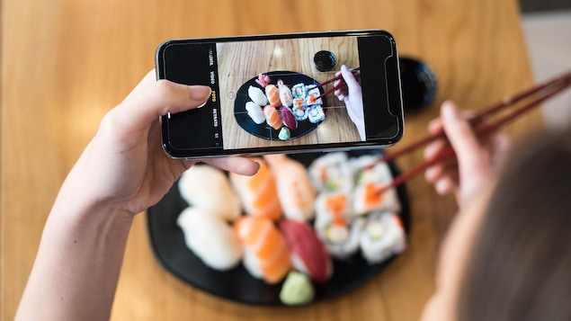 Une femme prend des sushis en photo avec son téléphone intelligent.