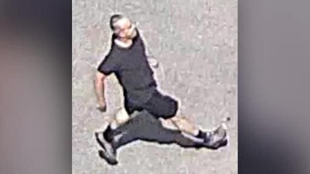 Un homme habillé en noir marche dans la rue.