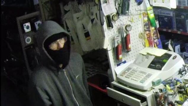 Un suspect filmé par une caméra de surveillance dans un commerce cambriolé.