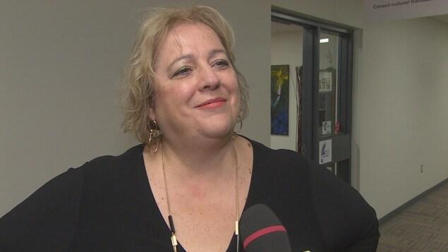 Suzanne Campagne se tient debout et sourit durant une entrevue.