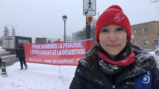 Suzanne Tremblay se tient debout devant une banderole de manifestation.