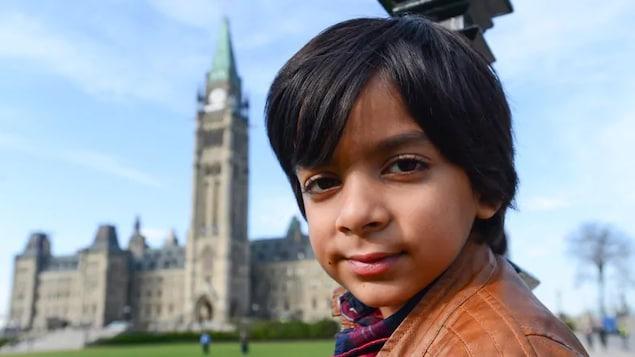 Syed Adam Ahmed regarde l'objectif. Derrière lui, le parlement.