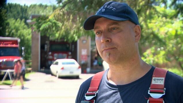 Sylvain Bourgeois, du Service d'incendie de Montebello, répond aux questions d'une journaliste devant une caserne.