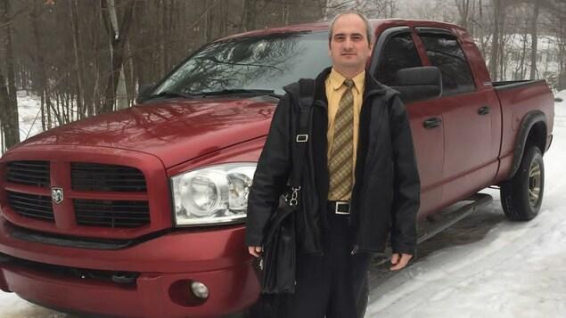 Un homme portant une chemise jaune et un manteau noir pose avec un sac en bandoulière devant une camionnette rouge vin.
