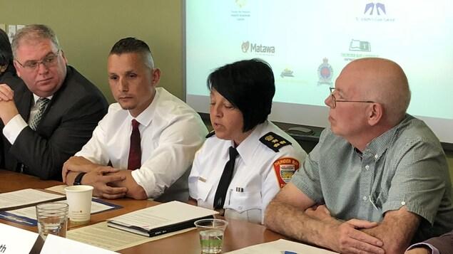 Une policière en conférence de presse conjointe avec plusieurs autres personnes en train de lire une déclaration.