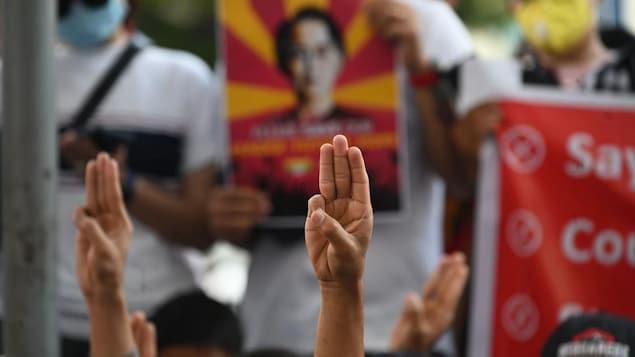 Dans un foule, des mains s'élèvent et font le signe des trois doigts levés.
