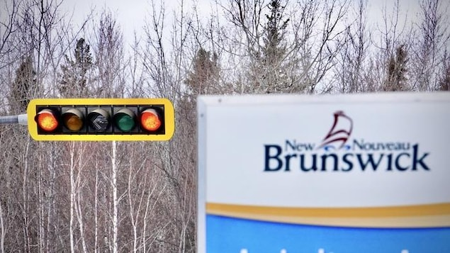Un feu de circulation au rouge, à côté d'une pancarte indiquant le Nouveau-Brunswick.