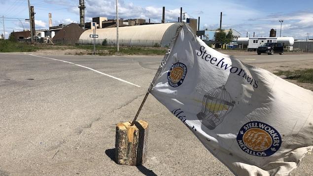 Drapeau du syndicat des Métallos planté de l'autre côté de la rue, face à la fonderie.