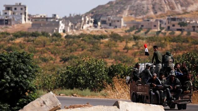 Quelques soldats sont assis dans la boîte arrière d'une camionnette qui roule sur une petite route dans un village de Syrie.