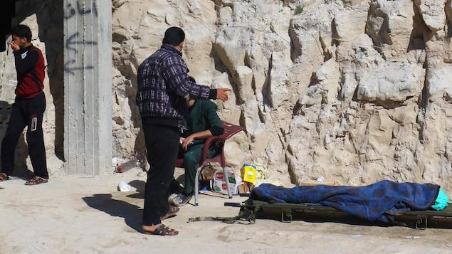 Des gens se tiennent près d'un corps inerte, victime d'une possible attaque au gaz près d'Idlib en Syrie.