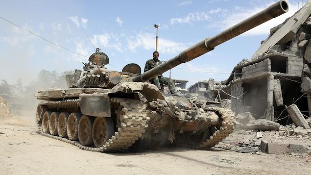 Un soldat est assis sur le devant d'un véhicule blindé.