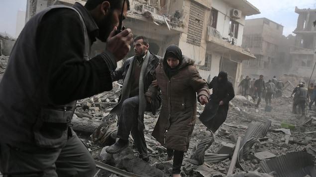 Des gens enjambent des décombres qui jonchent le sol,  dans un paysage de désolation.