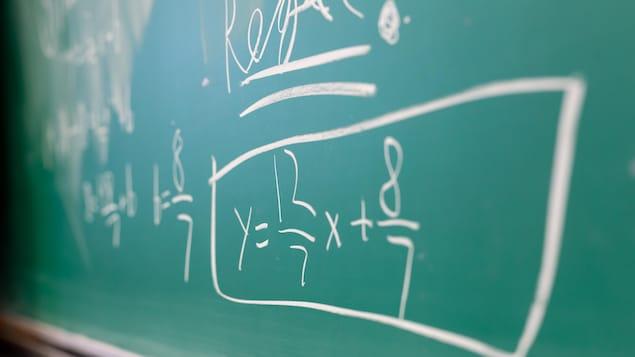 Une équation mathématique est inscrite sur un tableau vert.