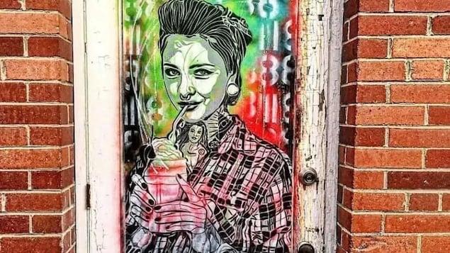 Le portait d'une femme peint dans un style urbain sur une porte.