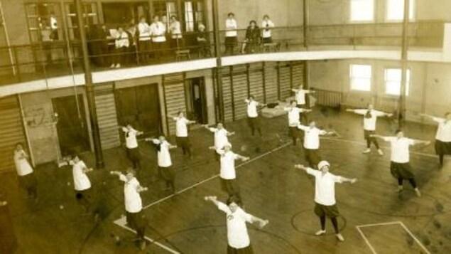Des étudiantes des arts ménagers lors d'une classe de conditionnement physique dans le gymnase pour femmes du Taché Hall
