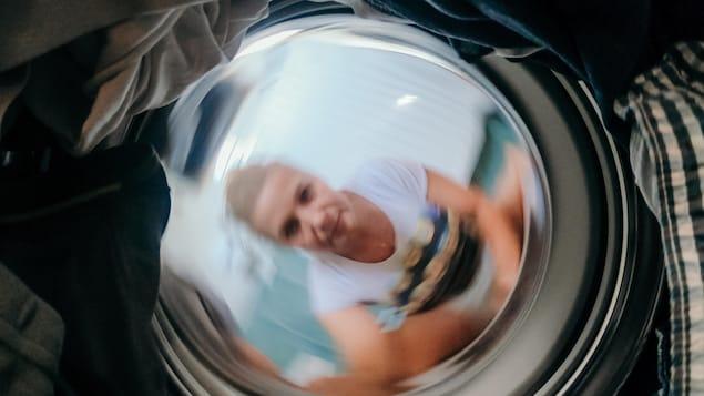Une femme observe sa lessive tourner dans la laveuse.
