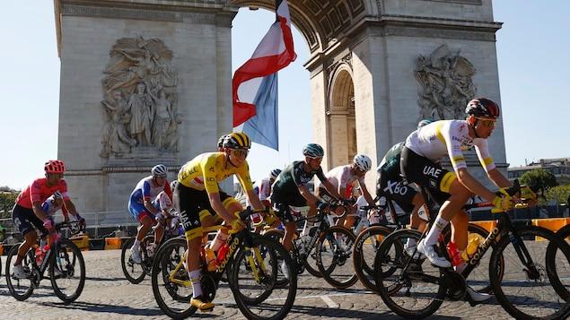 Un peloton roule devant l'Arc de Triomphe à Paris.