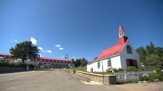 Au premier plan, la petite chapelle de bois et derrière, l'hôtel de deux étages avec ses nombreuses lucarnes.