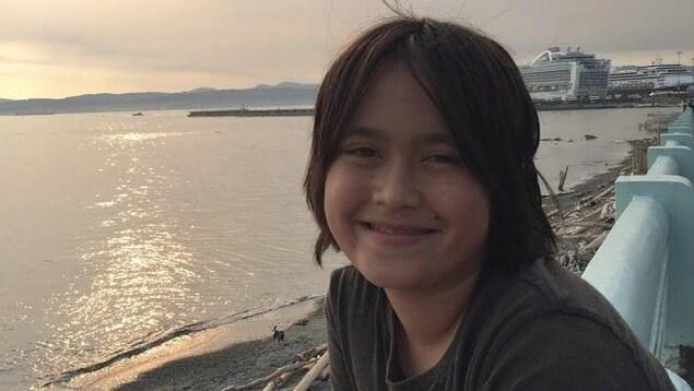 Photo d'un jeune homme au bord de l'eau.