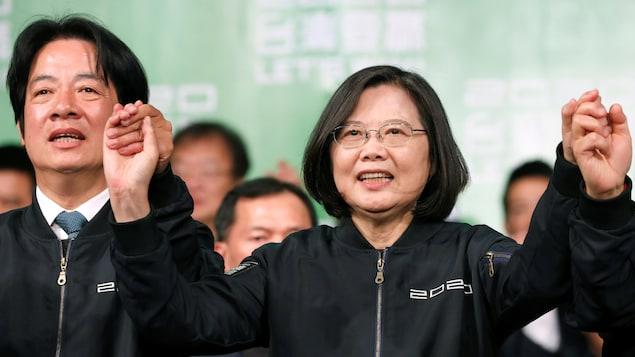 L'homme et la femme se tiennent par la main, les bras levés en signe de victoire.