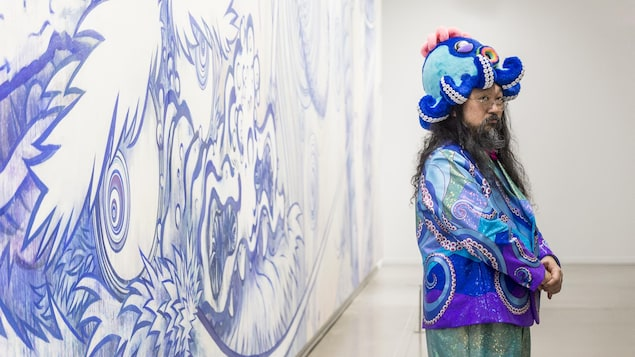 Un homme en costume brillant turquoise et mauve avec un chapeau de pieuvre pose de profil.
