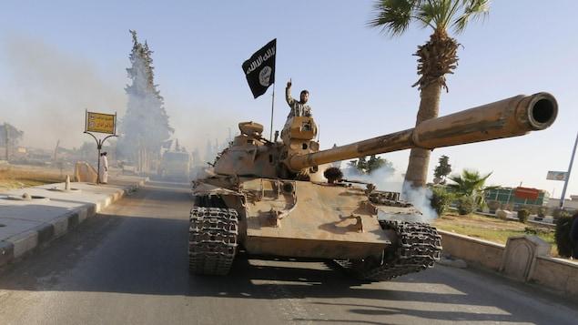 Un militant du groupe armé État islamique sur un tank dans la ville de Raqqa en Syrie en juin 2014