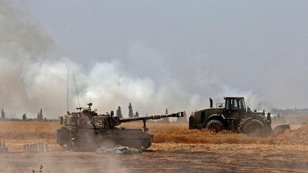 Un tank et un tracteur dans un champ. De la fumée flotte dans les airs.