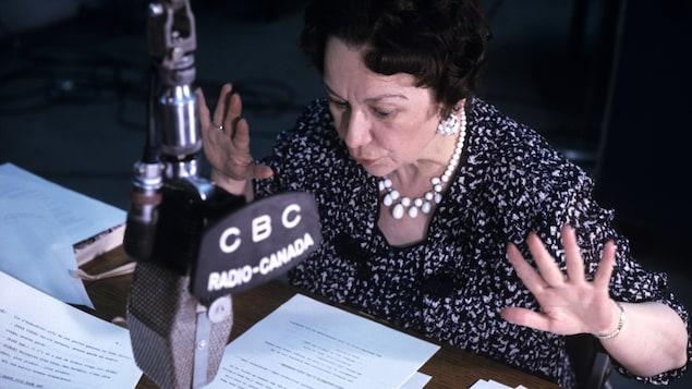 Dans un studio de radio, Lucille Desparois, assise à un pupitre, lit une histoire, les mains en action. Un micro est suspendu devant elle.