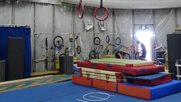 Le photo montre une pile de tapis d'entraînement placés sous des anneaux de voltige.