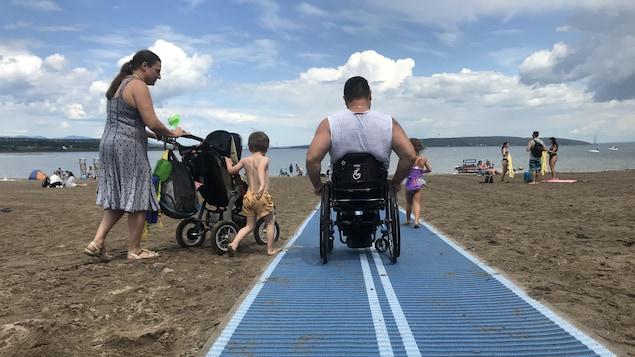 Un homme en fauteuil roulant sur un tapis placé sur le sable d'une plage. Il est avec sa femme et ses enfants.