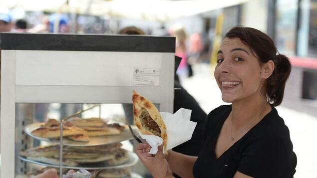 Une femme vend de la nourriture de rue grecque sur l'avenue Danforth