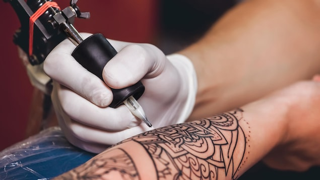Un gros plan sur le bras d'une personne en train de se faire tatouer.
