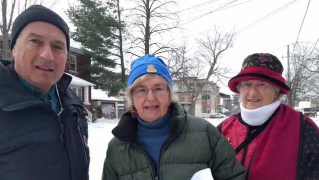 Trois personnes posent pour la caméra à l'extérieur, l'hiver.