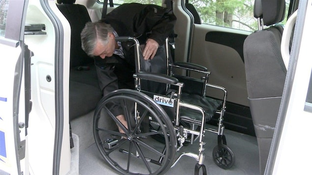 Le copropriétaire de Taxi-Multi, Maurice Gauvin, installe un fauteuil roulant dans son taxi adapté.