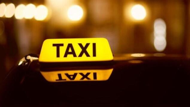 Enseigne d'un taxi allumé la nuit.