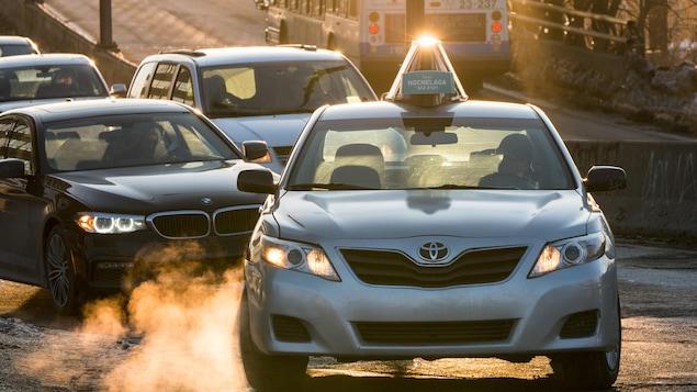 Un véhicule de la compagnie Taxi Hochelaga conduit devant plusieurs autres voitures.