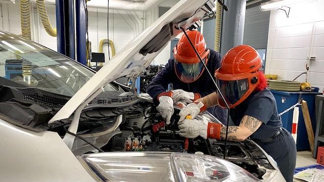 Deux élèves en train de travailler sur le moteur d'une voiture électrique.