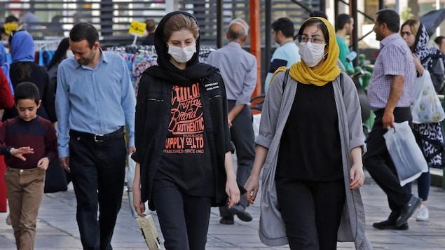 Des femmes et des hommes portant ou non un couvre-visage circulent  dans une rue de Téhéran.