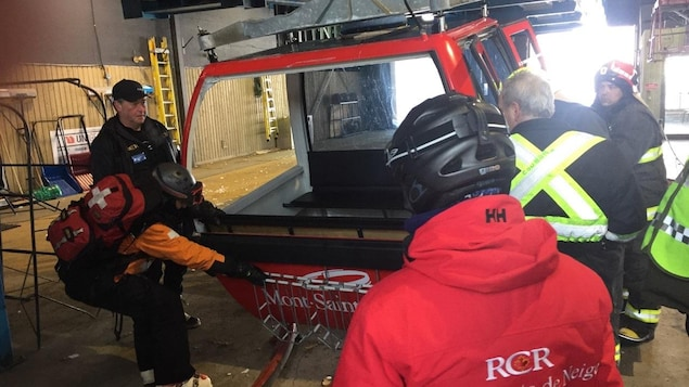 Une télécabine sans ses fenêtres se fait inspecter par les services d'urgence.