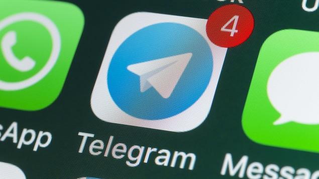 Une photo en gros plan d'un écran de téléphone sur lequel sont affichées les icônes de différentes applications de messagerie, dont celle de Telegram.