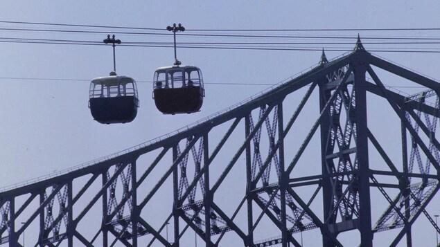 Deux nacelles de téléphériques sur leur fil avec en arrière-plan le pont Jacques-Cartier.