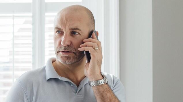 Un homme debout près d'une fenêtre parle au téléphone avec un air inquiet.