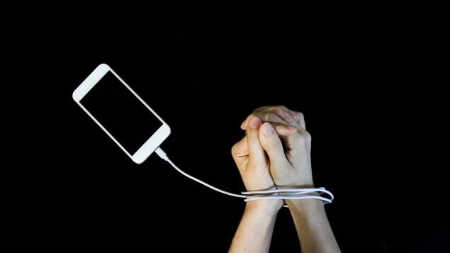 Des mains prises dans un fil de recharge, comme des menottes, branché à un téléphone.